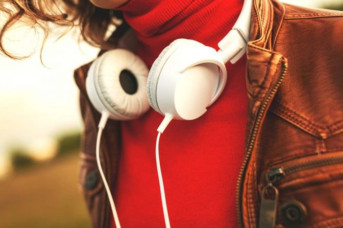 woman in red with headphones around neck