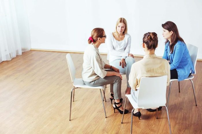 Women in support group sit on chairs