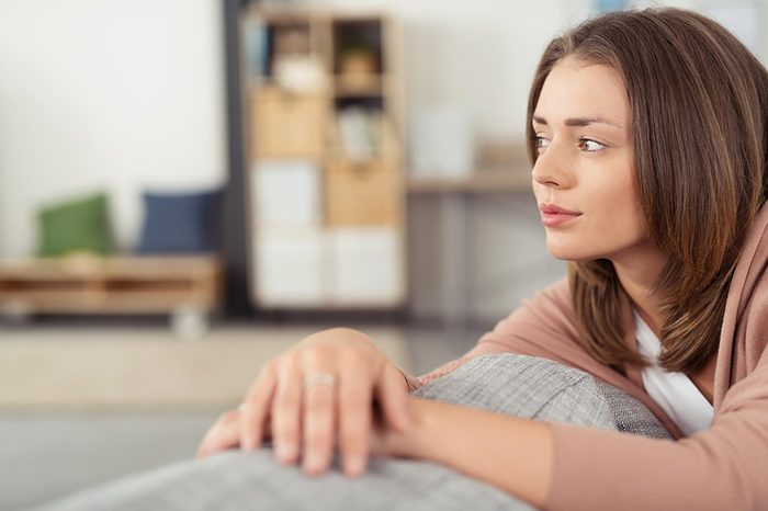 woman sitting on couch looking pensive