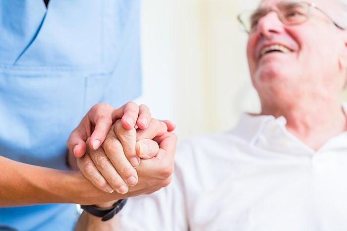 patient's hand held by healthcare worker