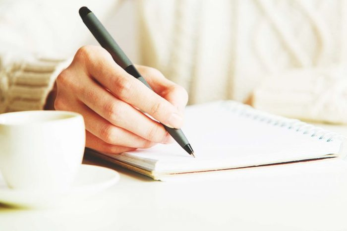person writing in journal