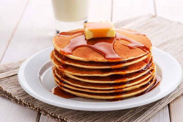 Stack of pancakes with butter and syrup on plate