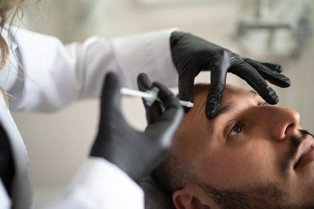 plastic surgeon injecting man's face with filler botox
