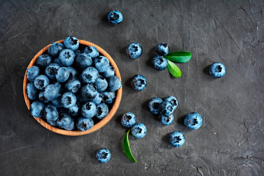 bowl of blueberries and scattered blueberries on a dark background