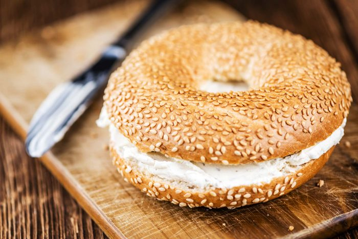 Sesame bagel with cream cheese.