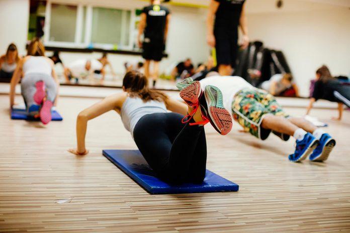 women and men in a workout class doing pushups