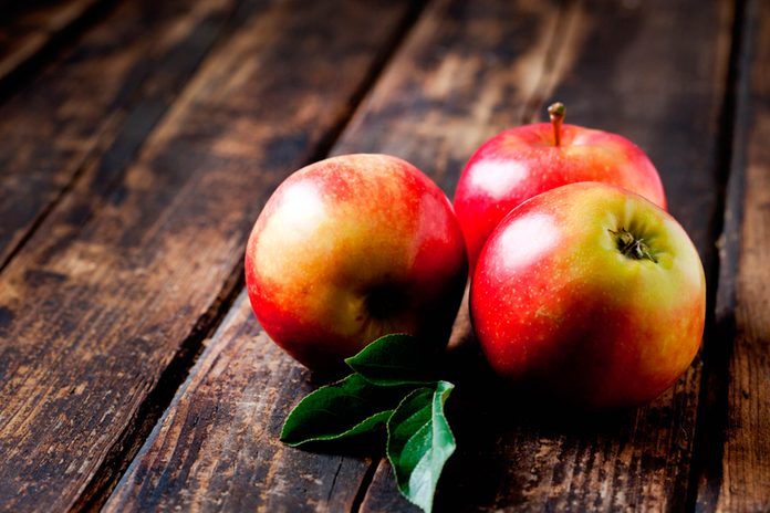 red apples on weathered wood table