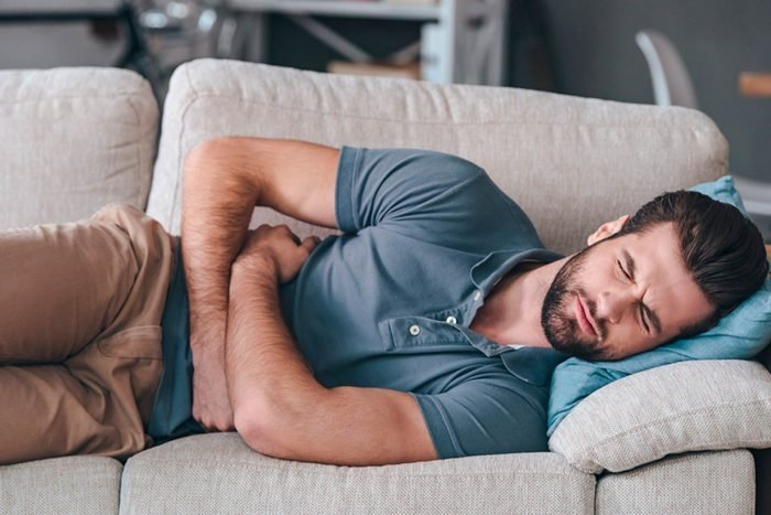 man clutching stomach lying on couch