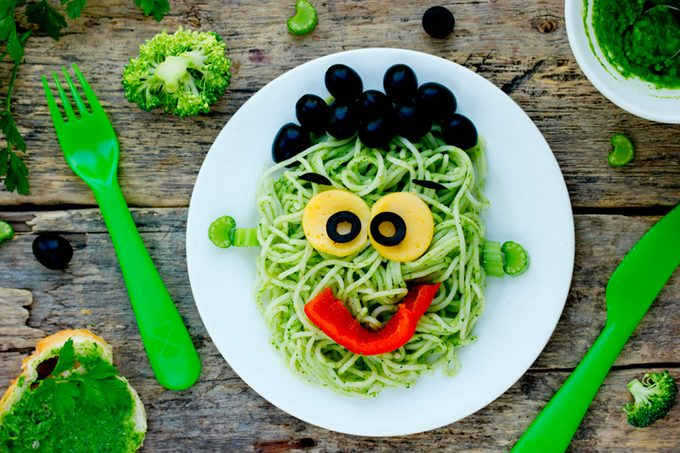 green pasta with a smiley face (yolk eyes, red pepper mouth, and olive hair)