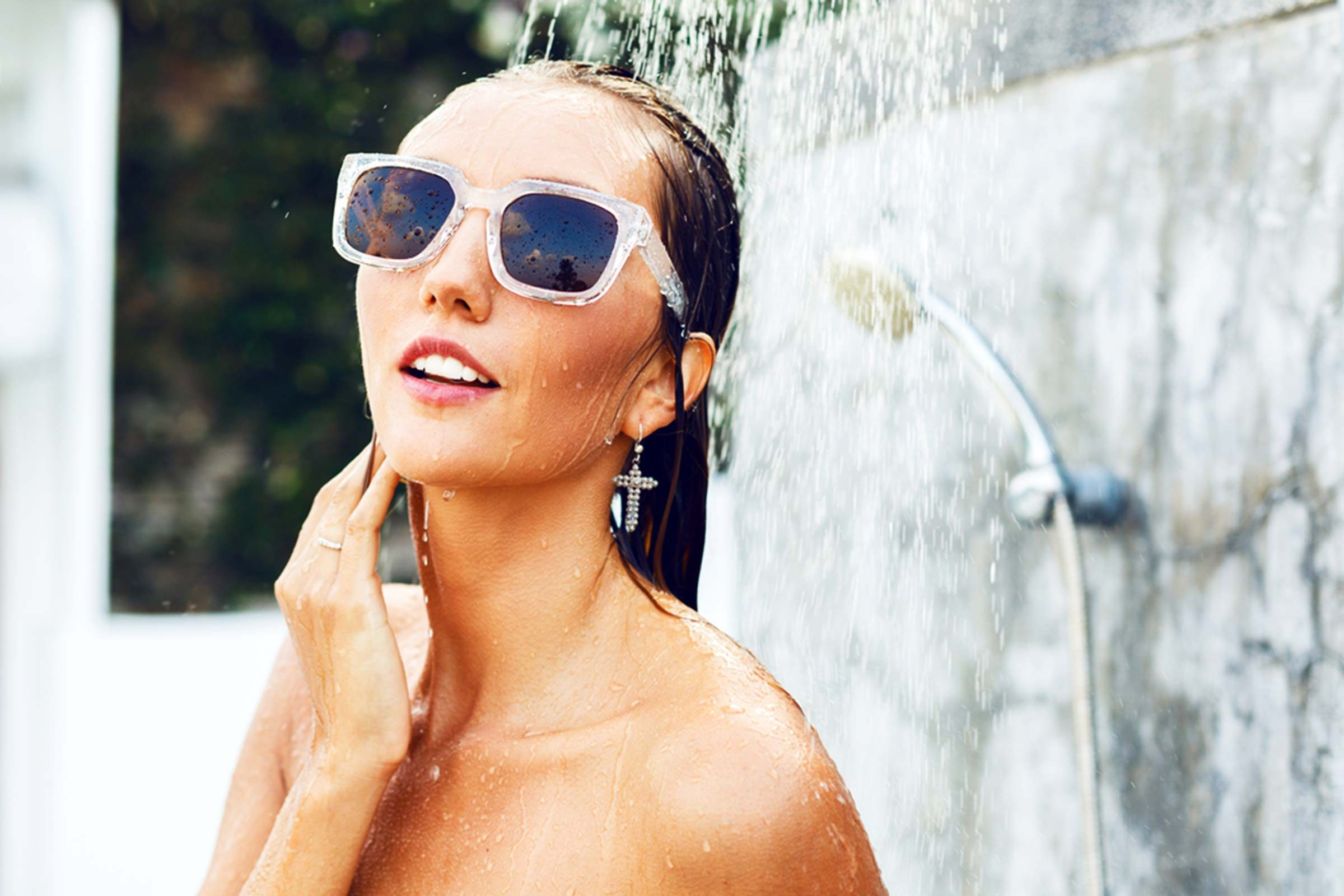woman wearing sunglasses in an outdoor shower