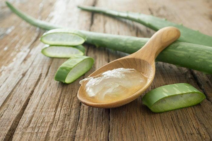 Aloe plant cut up, wooden spoon of aloe