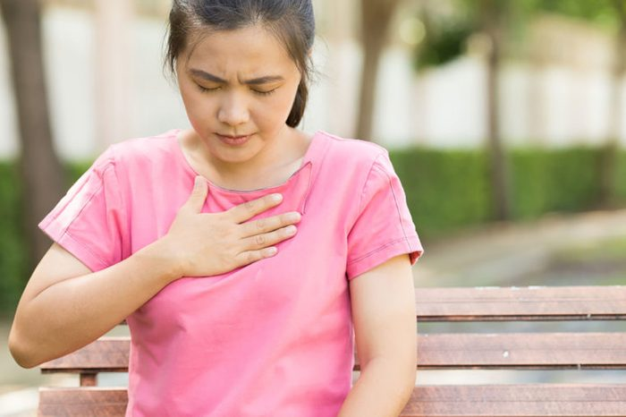 Asian woman holding her hand to her chest with a pained expression