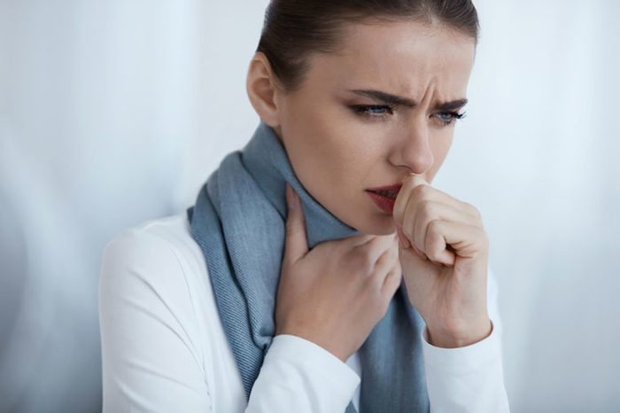 woman with one hand on her throat, and coughing into the other