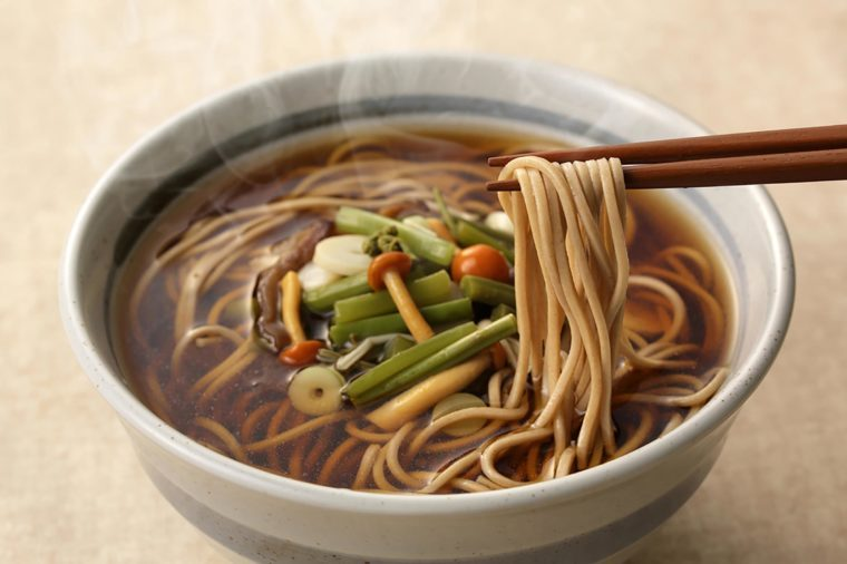 Soba noodles in a gray bowl with chopsticks.