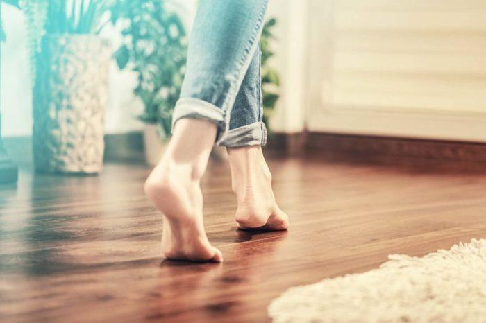 Woman walking barefoot on wood floor
