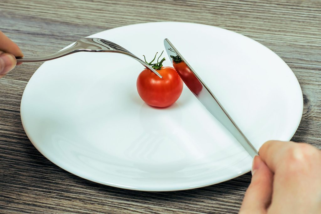 person using a knife and fork to eat a cherry tomato on a white plate