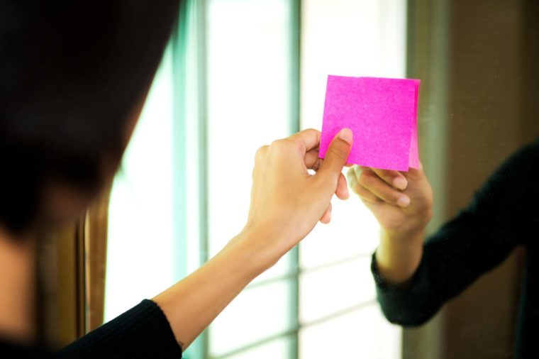 Woman placing pink Post-It on mirror