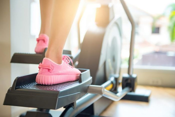 Woman in pink sneakers using the elliptical.