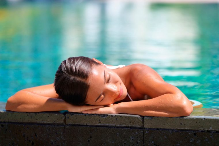 woman in a pool resting her head on the side