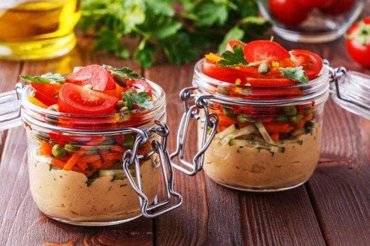 Snack-size jars of hummus and veggies.