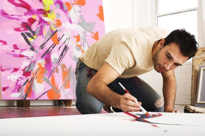 Male painter kneeling and painting canvas