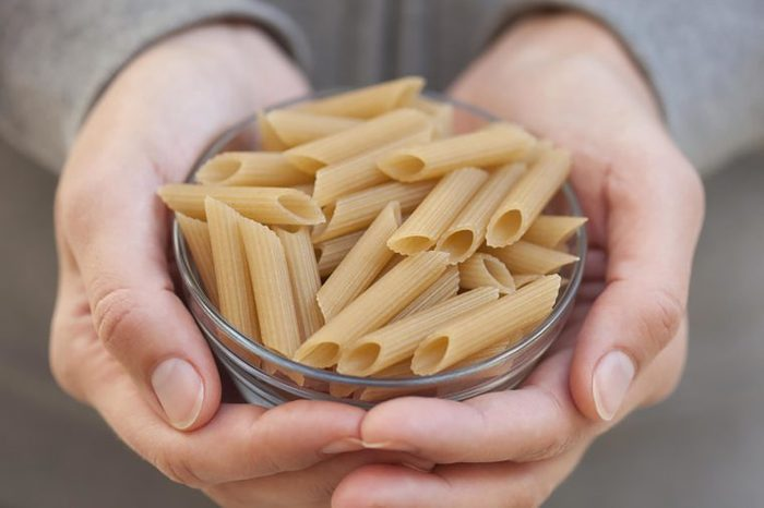 Person holding a bowl of brown rice noodles.