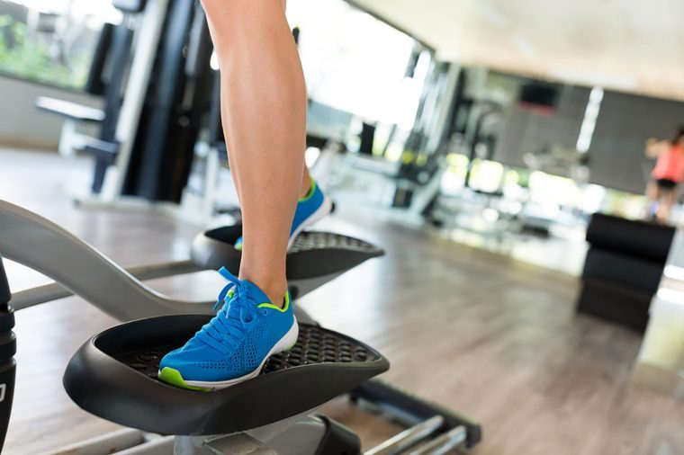 Woman in blue shoes using the elliptical.