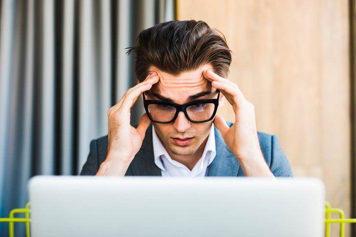 man in glasses at computer