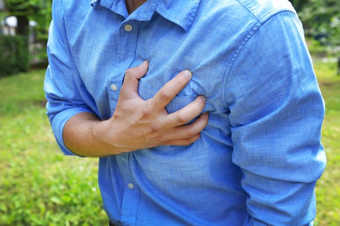 man clutching his chest inpain