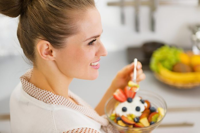 woman eating a bowl of fruit with yogurt