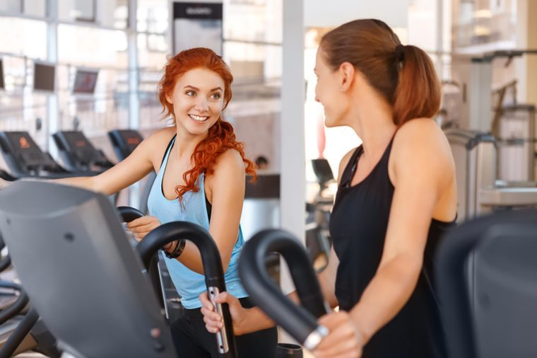 Two women talking on an elliptical at the gym.