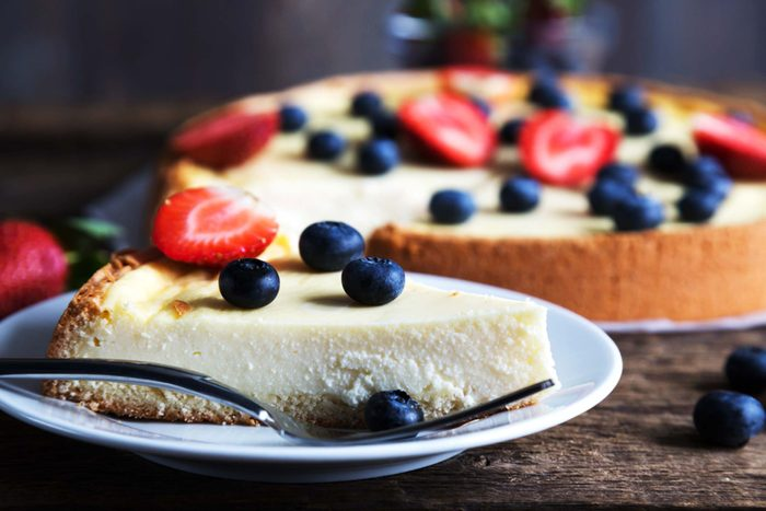 Cheesecake topped with fruit and a slice on a plate.