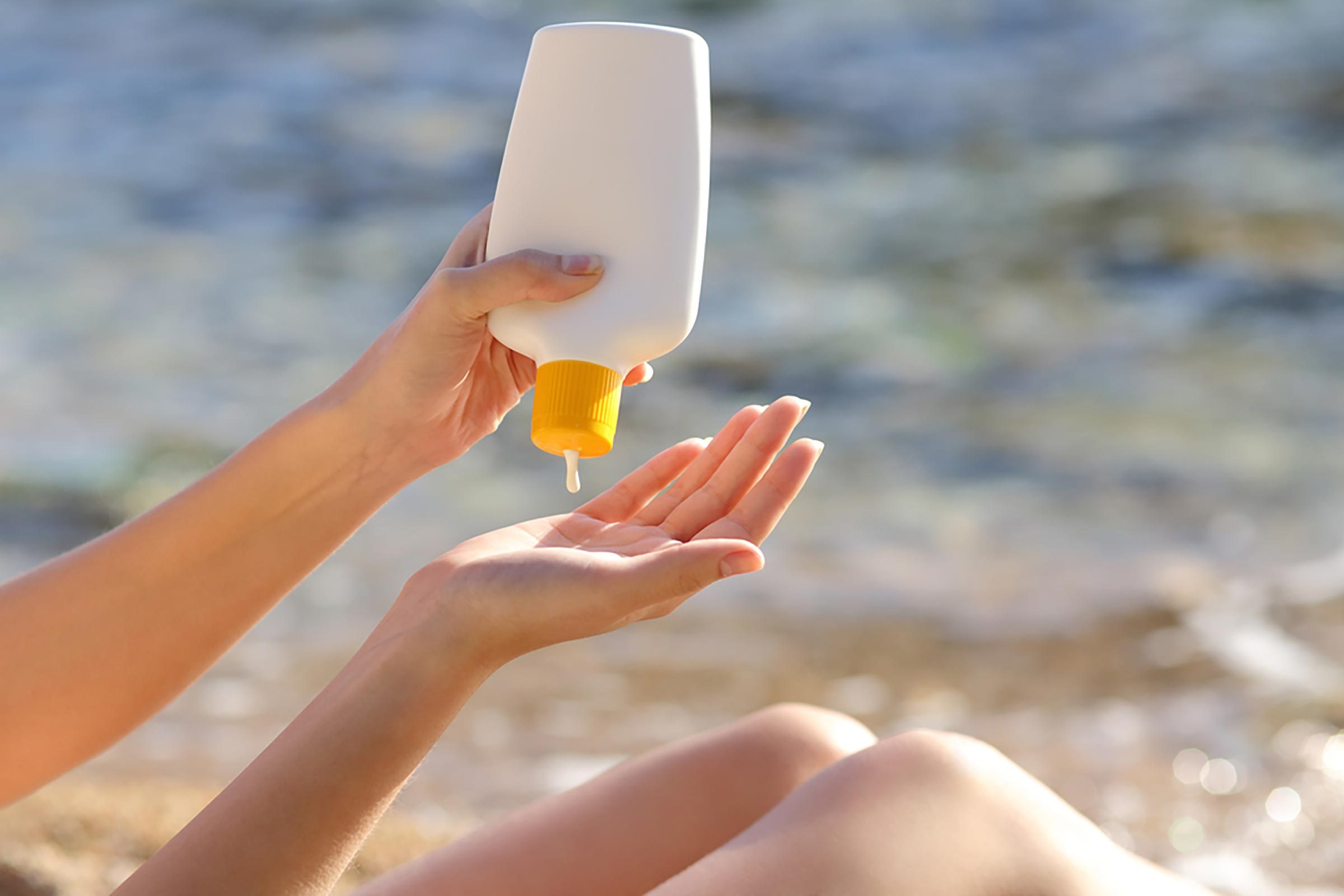 woman squeezing sunscreen into hand at the beach