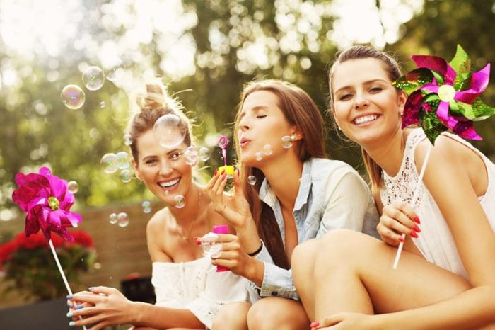 Three girlfriends with pinwheels and blowing bubbles
