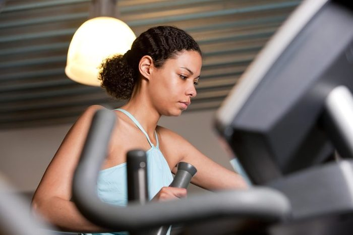 Woman in a blue tank top working out on an elliptical.