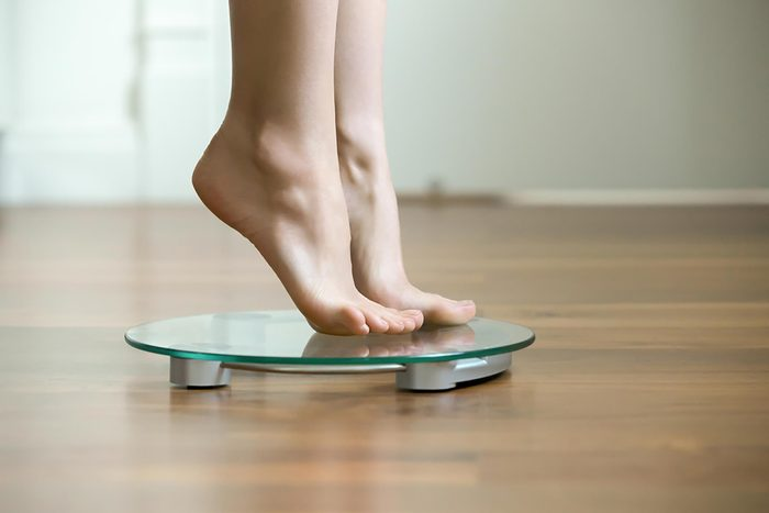 woman standing on tiptoes on a scale