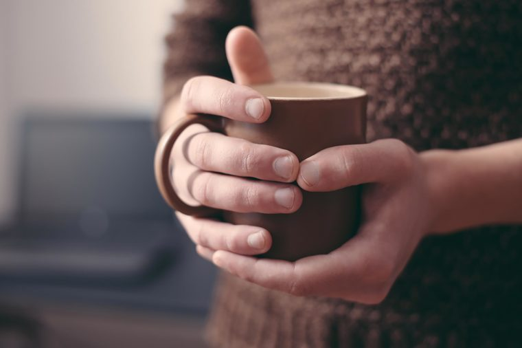 holding cup of coffee