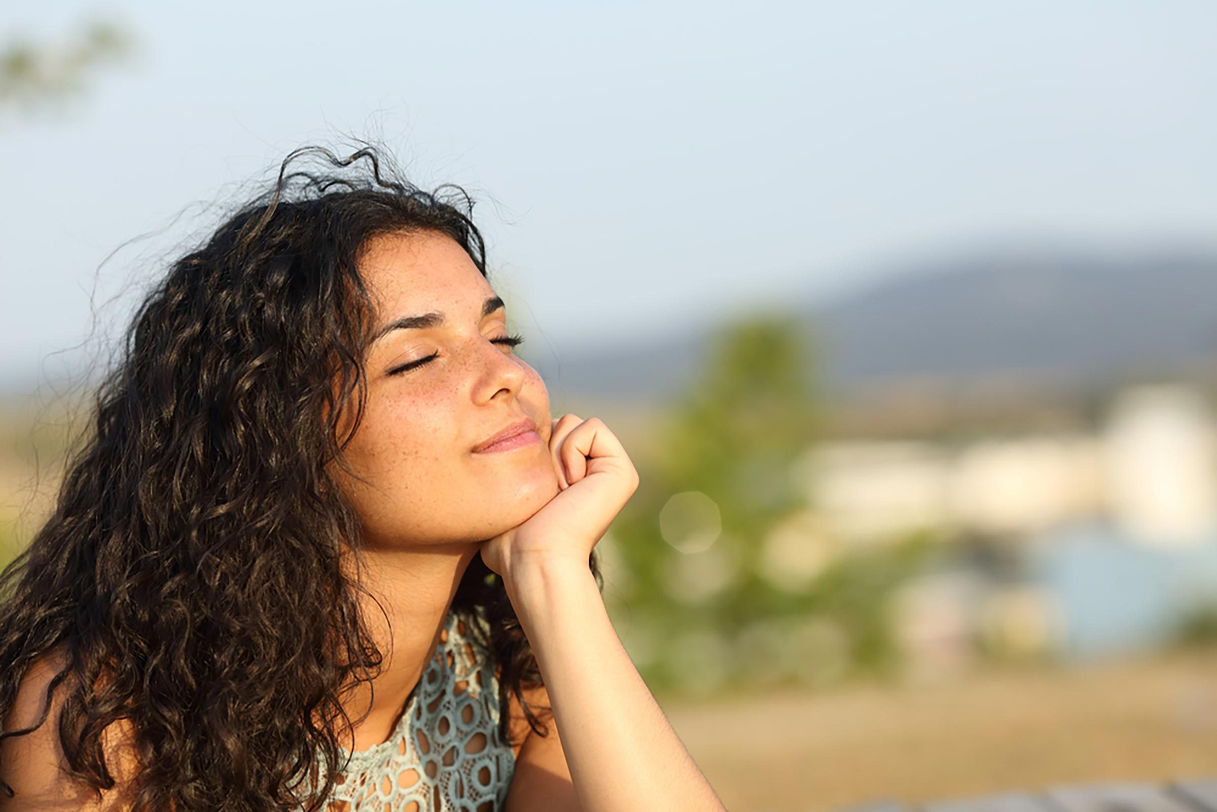 woman closes eyes in sun