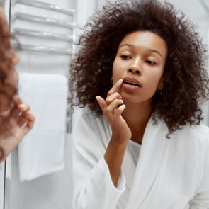 young woman looking at lips in the bathroom mirror
