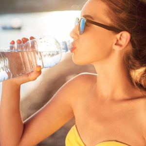 Woman in sunglasses sipping from a water bottle.