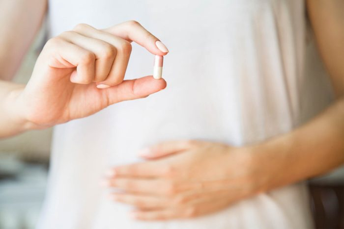 woman's hands holding capsule