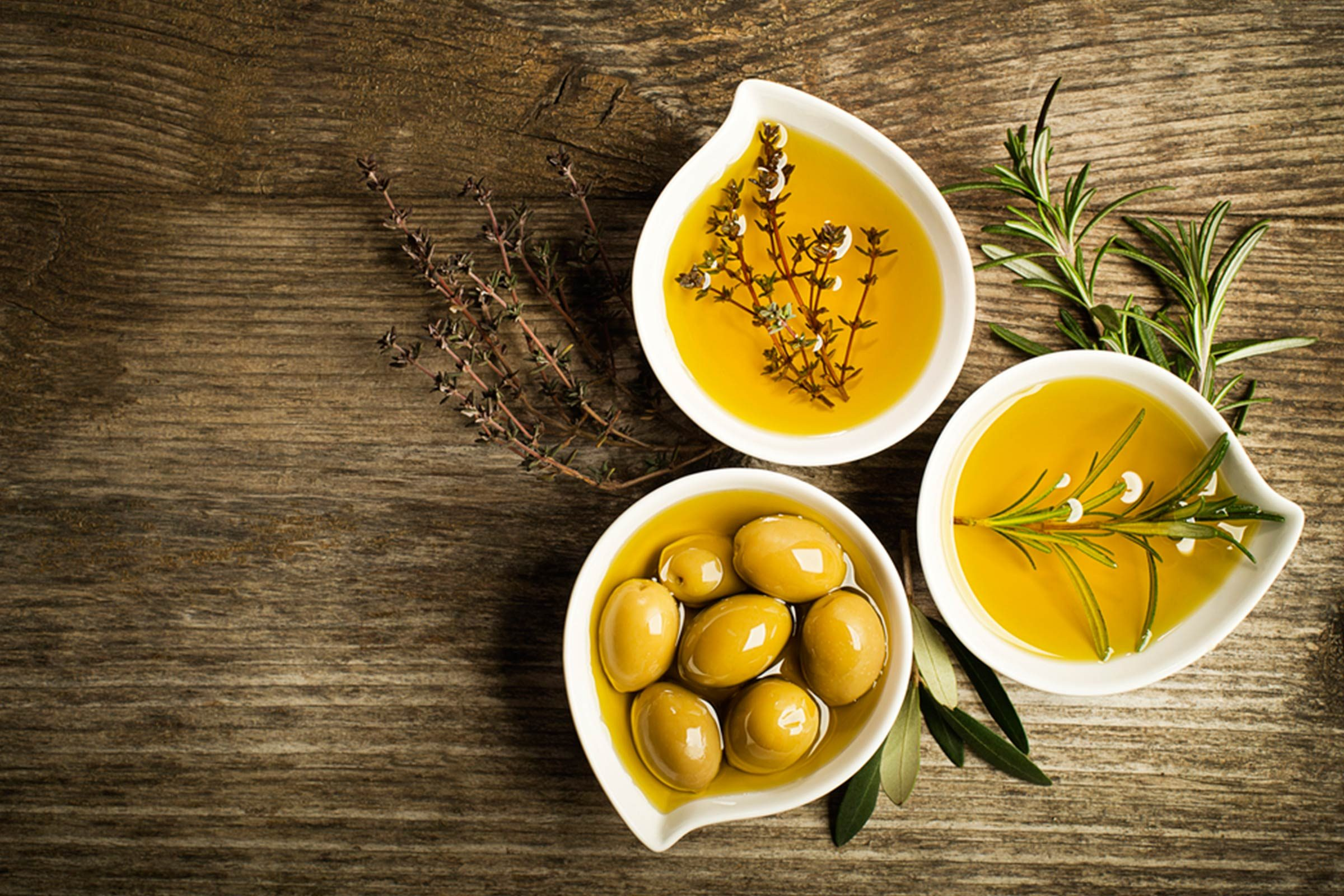 three bowls of olive oil with olives and spices
