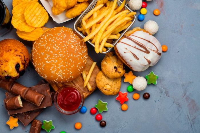 An array of junk food, including candy, cookies, chips, and fries.