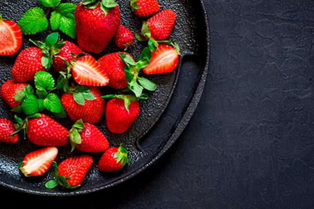 whole and halved strawberries on a plate