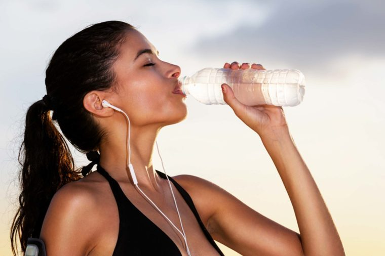 woman with earbuds in workout gear, drinking from a bottle of water
