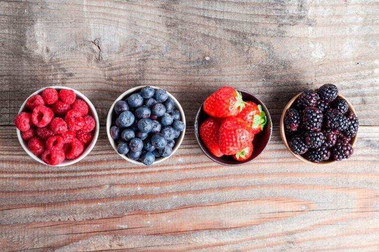 Ramekins of raspberries, blueberries, strawberries, and blackberries.