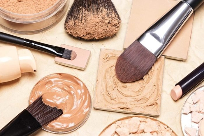 Makeup brushes in foundation palettes.