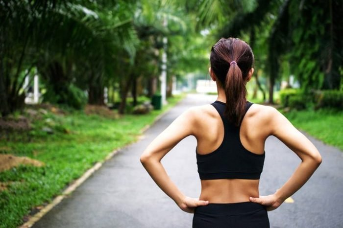Woman in workout gear outdoors, shot from behind