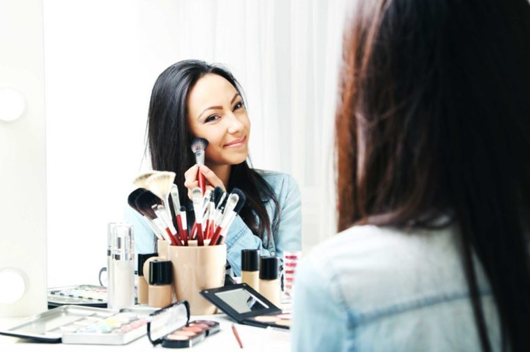 Woman applying makeup to her face in front of a mirror.