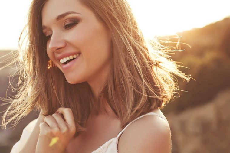 attractive brunette woman laughing outdoors
